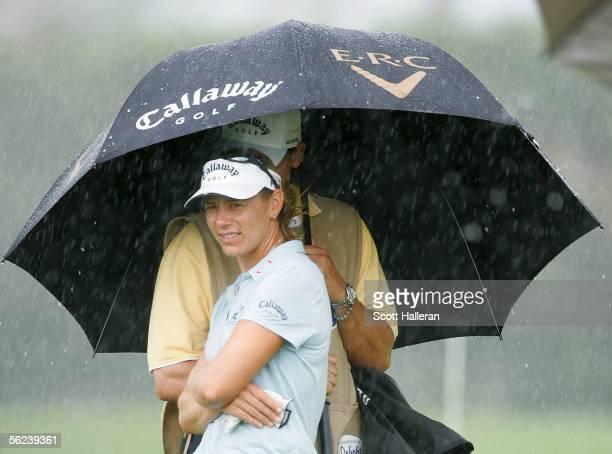 Annika Sorenstam of Sweden waits under an umbrella on the sixth green during the third round of the ADT Championship at Trump International Golf Club...