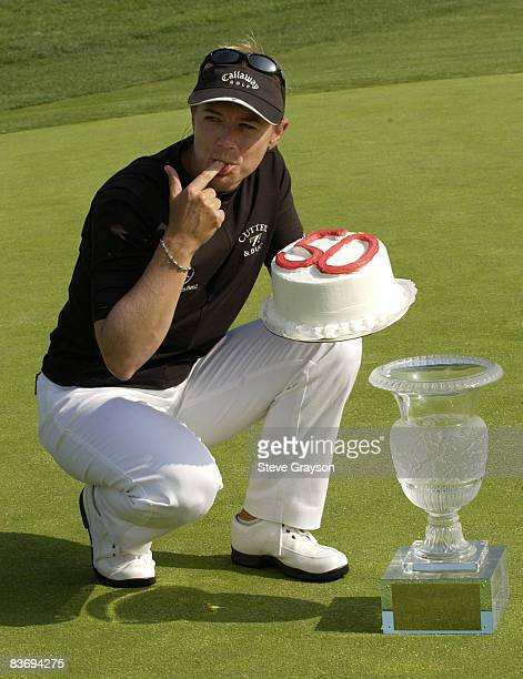 Annika Sorenstam poses with a cake marking her 50th LPGA career win and the winner's trophy on the 18th green after winning the LPGA's 2004 Office...