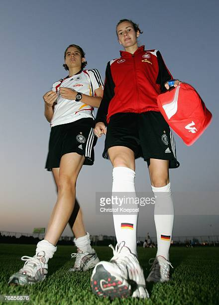 Annike Krahn and Simone Laudehr walk off the pitch after the Women's German National Team training session on the training ground at the Wuhan Sports...