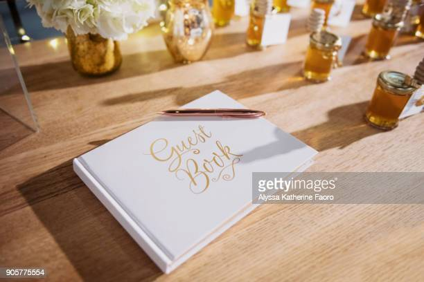 Anniversary Party Scene - White guestbook with rose gold pen on a wooden table