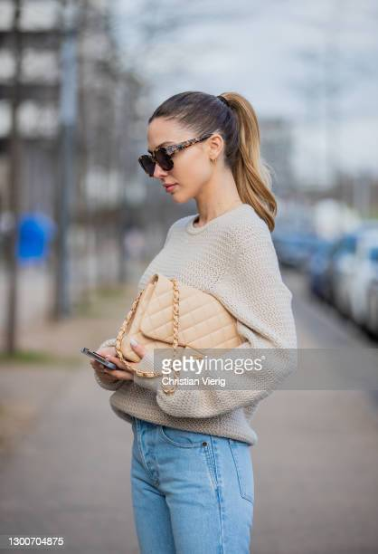 Ann-Kathrin Götze is seen looking on her Apple Iphone 12 wearing beige Ferragamo jumper, denim jeans Saint Laurent, Chanel bag in beige, sunglasses...