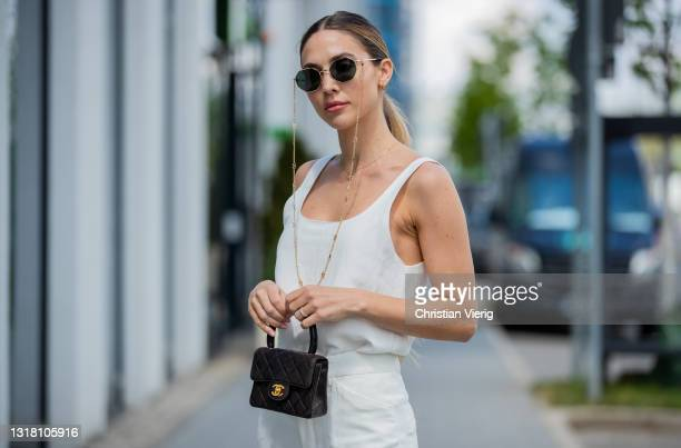 Ann-Kathrin Götze is seen wearing black Chanel hat, white top and pants Zara, black Chanel bag and sneaker, Valentino sunglasses on May 14, 2021 in...
