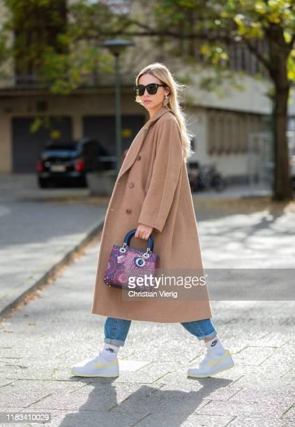 Ann-Kathrin Götze is seen wearing brown coat Aritzia, Celine earrings, Nike sneaker, red Dior bag, Dior sunglasses, Mango denim jeans on October 25,...