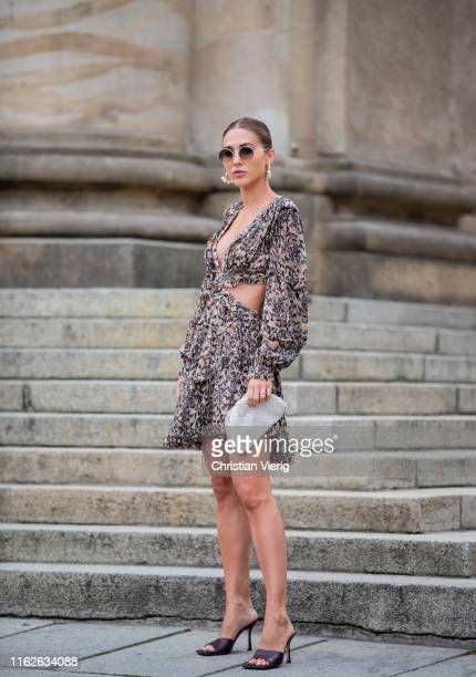 Ann-Kathrin Götze is seen wearing Zimermann dress with animal print, pouch and sandals Bottega Veneta, sunglasses Olivers People x The Row, earrings...