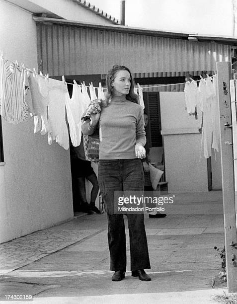 Announcer Aba Cercato makes her way with the jacket posed on the shoulders behind her hangs a line of freshly laundered clothes Fregene 1971