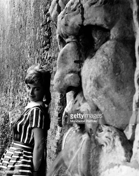 Announcer Aba Cercato poses smiling against a wall while from the stone in relief emerges a face of a man June 1960
