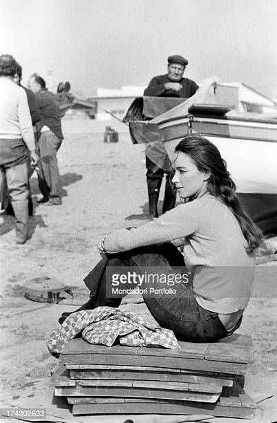 Announcer Aba Cercato sits on woods splints on the beach lost in her thoughts nearby fishermen hum with activities and a boat is beached Fregene 1971