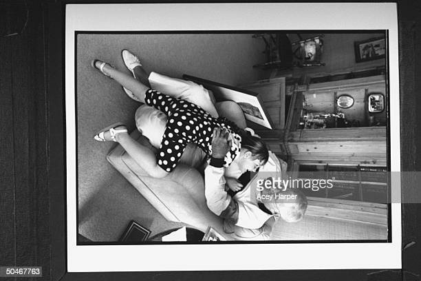TV announcer Ed McMahon cuddling w his 5yrold adopted daughter Katherine as he sits in easy chair at home