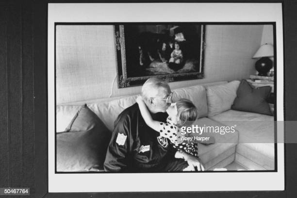 TV announcer Ed McMahon getting a kiss from w his 5yrold adopted daughter Katherine as he sits in on couch at home