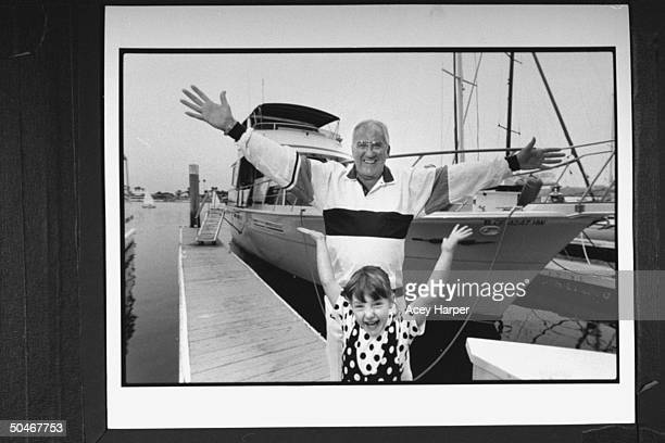 TV announcer Ed McMahon posing w his adopted daughter Katherine both w outstretched arm as they stand on dock in front of his 50ft ChrisCraft yacht...