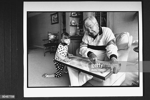 TV announcer Ed McMahon showing picture to his 5yrold adopted daughter Katherine at home