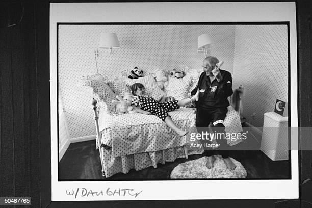 TV announcer Ed McMahon taking the sandals off of his 5yrold adopted daughter Katherine as they sit together on bed in her bedroom at home