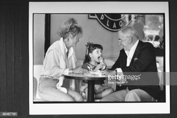 TV announcer Ed McMahon watching his 5yrold adopted daughter Katherine take a bite out of an ice cream cone as they sit at table w his exwife...