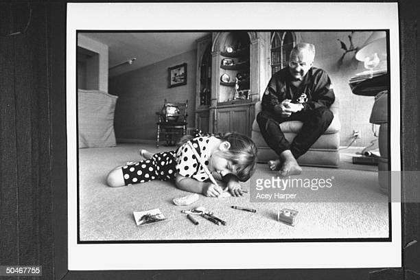TV announcer Ed McMahon watching his adopted 5yrold daughter Katherine write w a large pencil as she sits on the carpet before him in living room at...