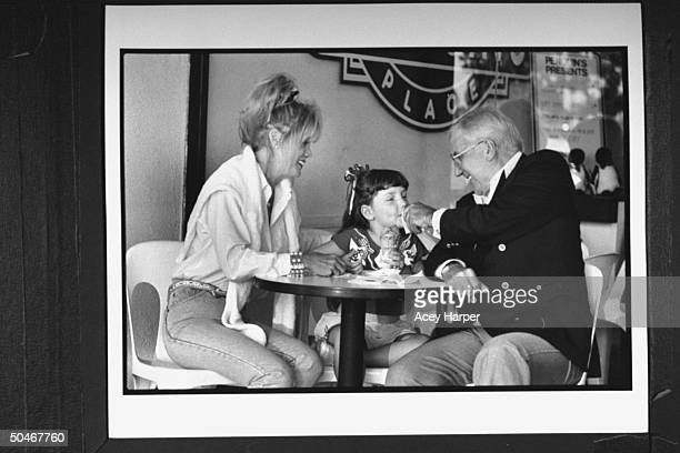 TV announcer Ed McMahon wiping his 5yrold adopted daughter Katherine's mouth as she holds an ice cream cone while his exwife Victoria looks on at...