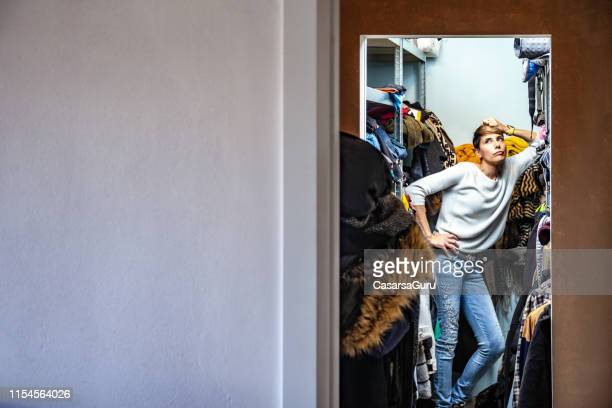 annoyed adult woman leaning on a shelf in her closet - closet stock pictures, royalty-free photos & images