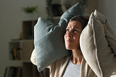 Annoyed adult woman suffering neighbour noise at night at home