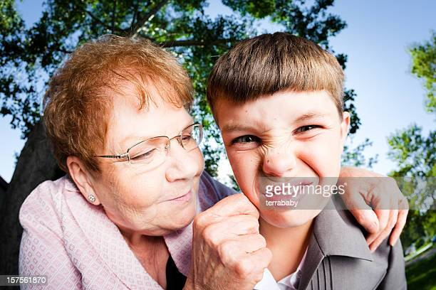 annoyed boy and loving grandmother - cheek stock pictures, royalty-free photos & images