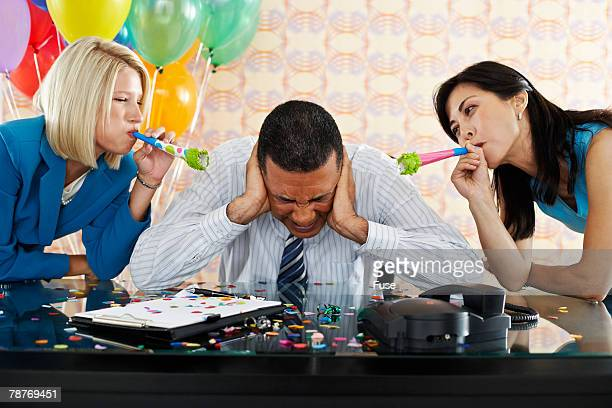 Annoyed Businessman Between two Women Using Party Blowers