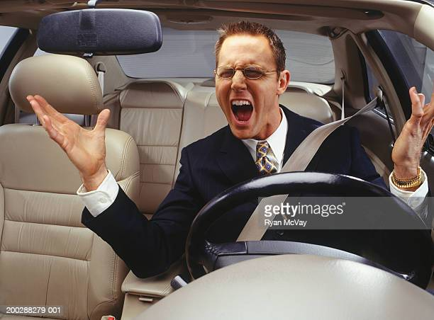 Annoyed businessman with road rage, shouting in car