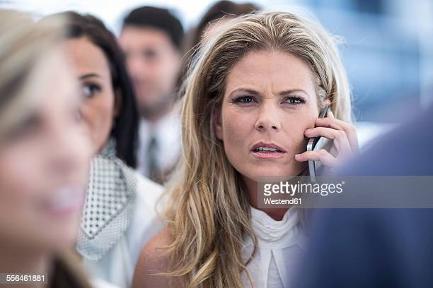 Annoyed businesswoman on cell phone in busy city