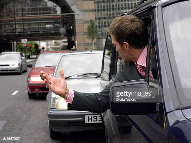 Annoyed Driver in a Traffic Jam Looking Behind and Gesturing
