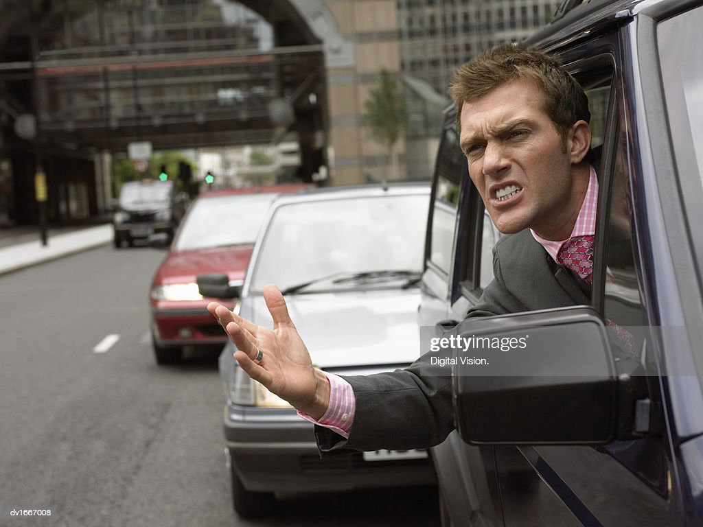 Annoyed Driver Looking out the Window Gesturing : Stock Photo