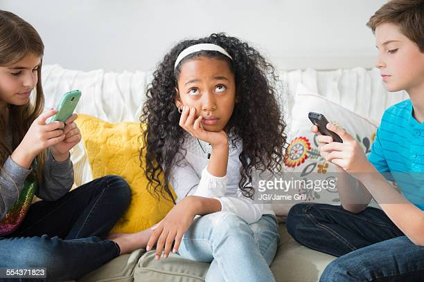 Annoyed girl ignoring friends using cell phones on sofa