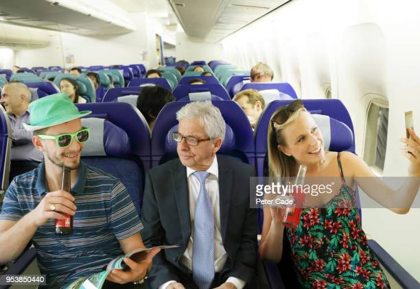 annoyed man on airplane between young adults - green dress stock pictures, royalty-free photos & images