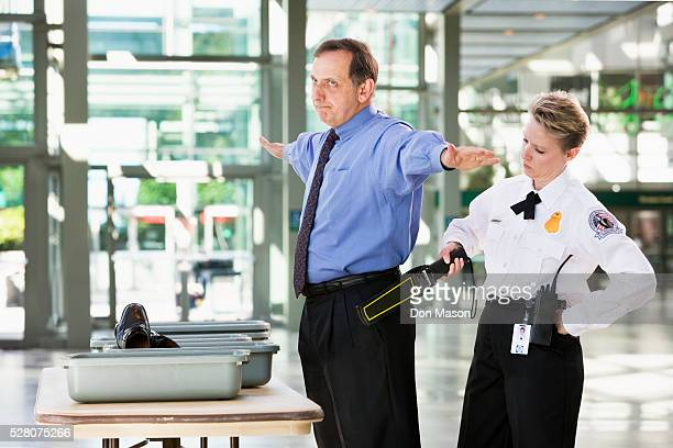 annoyed passenger being screened by security - security scanner stock pictures, royalty-free photos & images
