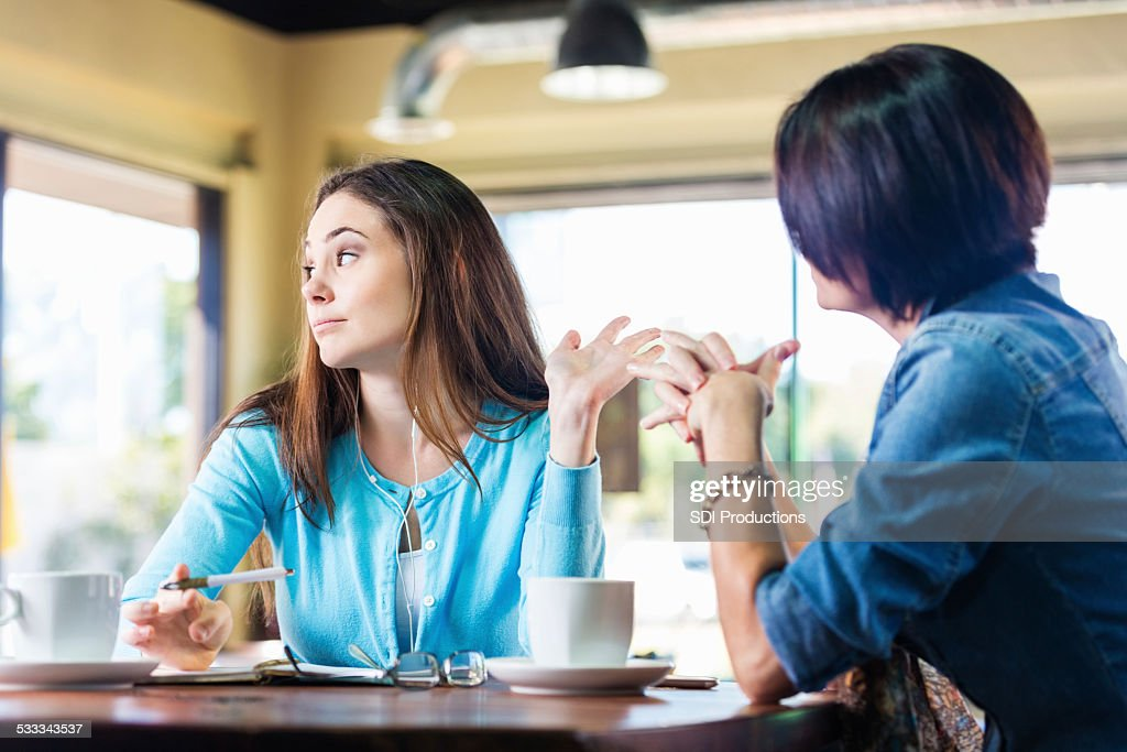 Annoyed teen girl talking to mother in coffee shop : Stock Photo