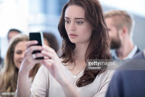 Annoyed woman looking on cell phone in busy city