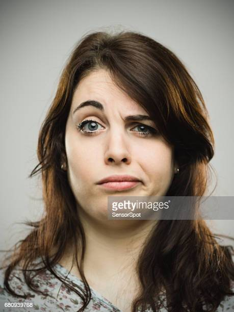 annoyed young female against gray background - frowning stock pictures, royalty-free photos & images