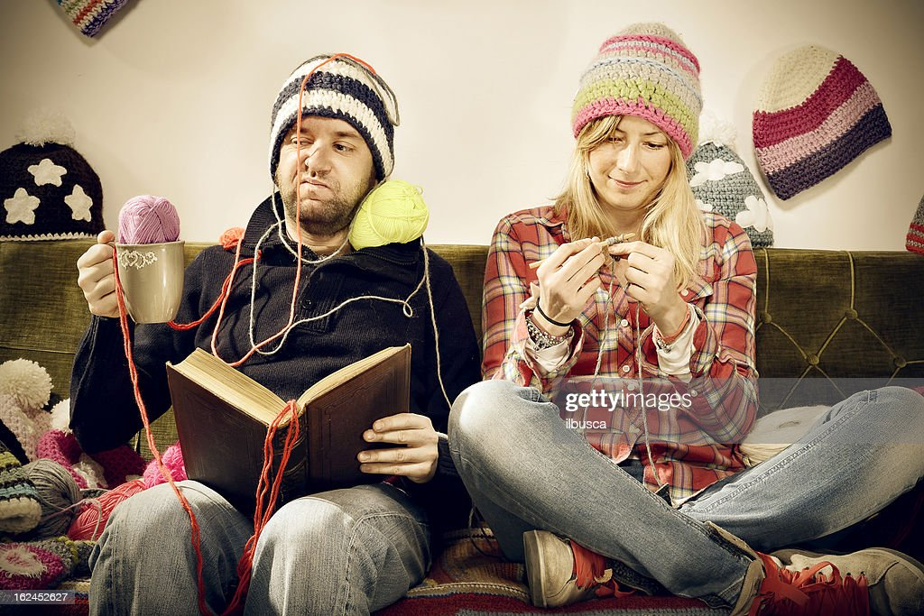Annoying young knitter woman couple portrait on couch : Stock Photo