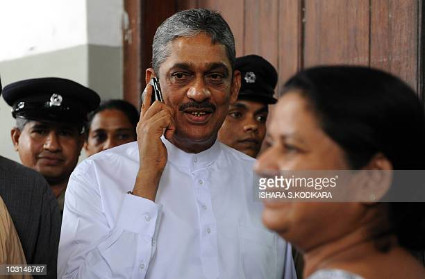 Anoma Fonseka looks on as her husband Sri Lanka's detained former army chief General Sarath Fonseka speaks on the phone as leaves a court in Colombo...