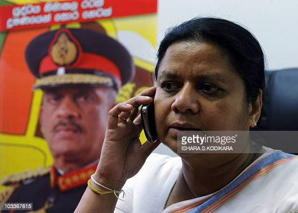 Anoma Fonseka wife of Sri Lanka's former army chief Sarath Fonseka whose portrait hangs behind her talks on her mobile phone at her home in Colombo...