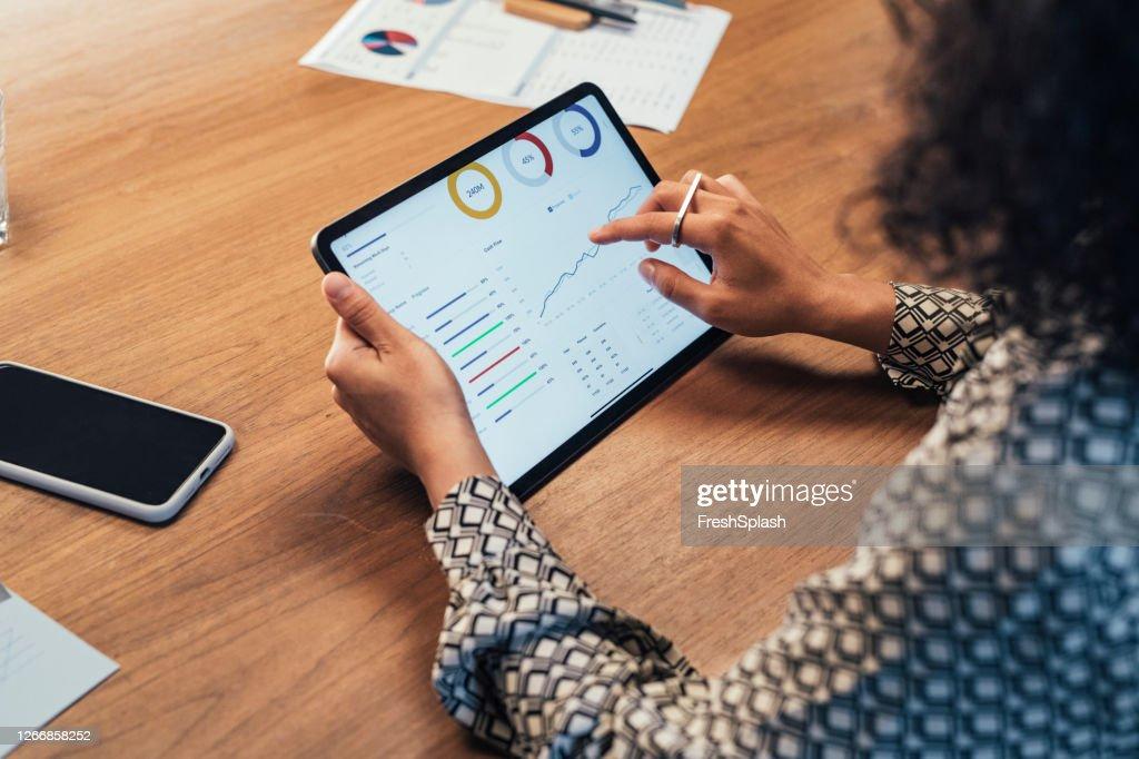 Anonieme onderneemster die statistische bedrijfsrapporten op haar Pc van de Tablet bij het Bureau analyseert, een Close Up : Stockfoto