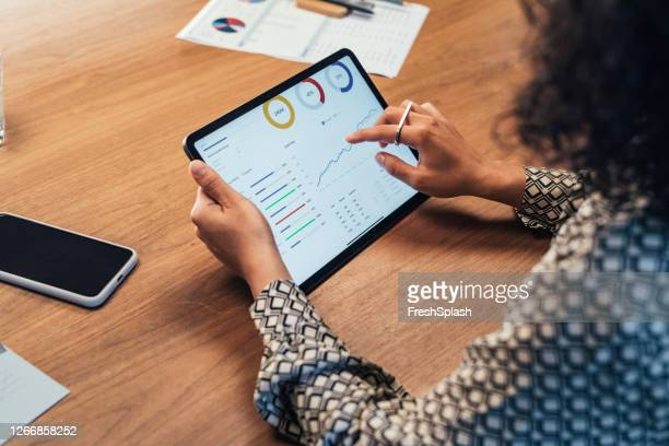 anonymous businesswoman analyzing statistical business reports on her tablet pc at the office, a close up - collection stock pictures, royalty-free photos & images