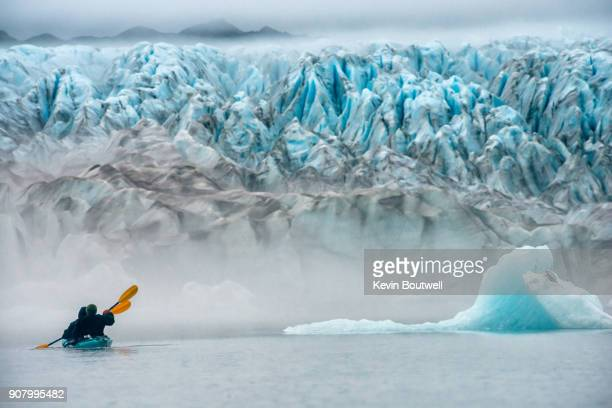 Anonymous couple kayaks toward a glacier rising from the mist