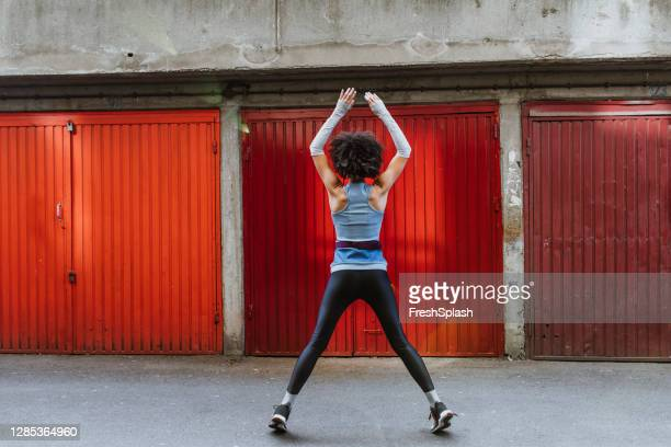 anonymous female athlete with an afro haircut doing jumping jacks outdoors - long sleeved stock pictures, royalty-free photos & images
