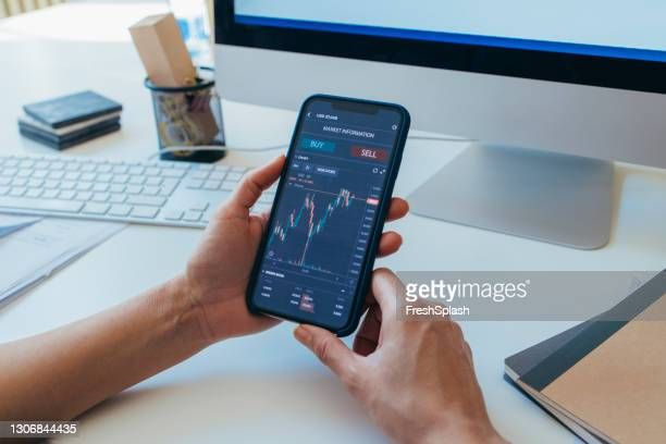 anonymous finance expert analyzing financial charts on a smartphone - cryptocurrency stock pictures, royalty-free photos & images
