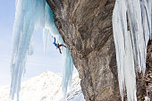 Anonymous man ice climbing on massive icicles
