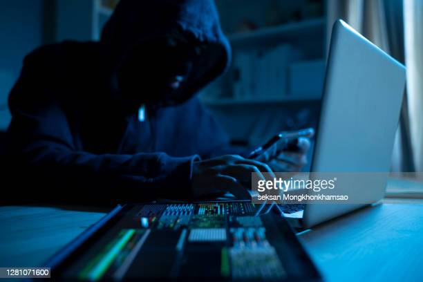 anonymous person in the hood sitting in front of computer working with laptop and mobile phone - gewalt stock-fotos und bilder