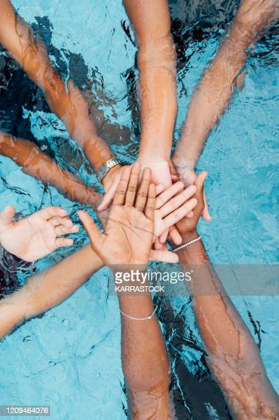 anonymous persons stacking hands - arrangement stock pictures, royalty-free photos & images