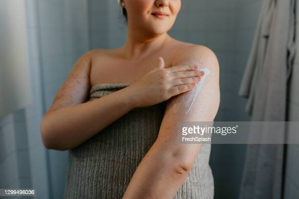 anonymous overweight woman applying body lotion after shower - dry skin stock pictures, royalty-free photos & images