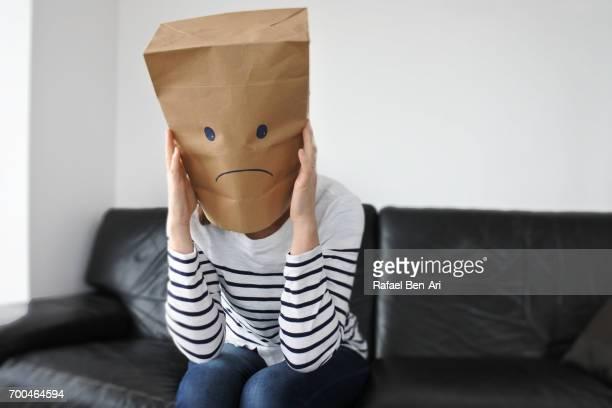 anonymous sad woman sitting on a couch - rafael ben ari fotografías e imágenes de stock