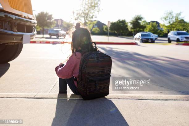 anonymous schoolgirl sits on curb by herself - schoolgirl stock pictures, royalty-free photos & images