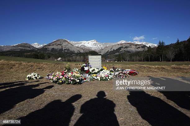 Anonymous stand near a stela commemorating the victims of the March 24 Germanwings Airbus A320 crash in the village of Le Vernet southeastern France...
