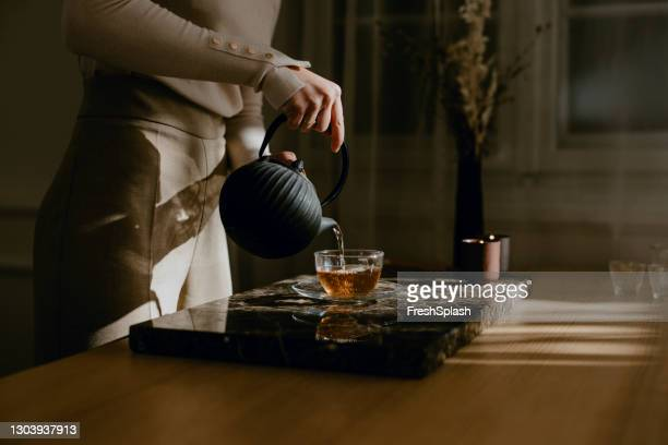 anonymous woman enjoying a slow afternoon, carefully pouring herself tea - ceremony stock pictures, royalty-free photos & images