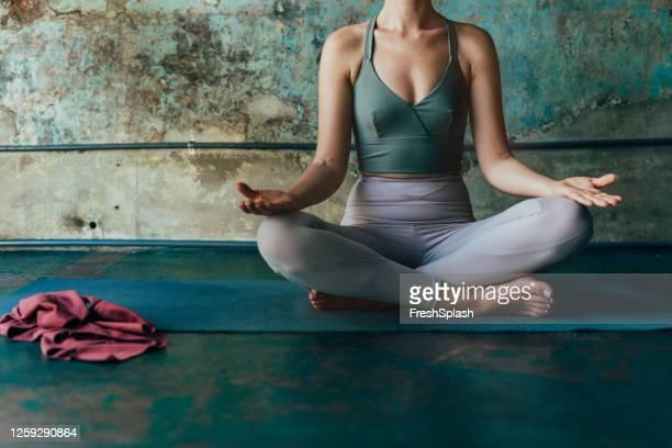 自宅で瞑想する匿名の女性、ロックダウンコンセプト中にアクティブに滞在 - レギンス ストックフォトと画像